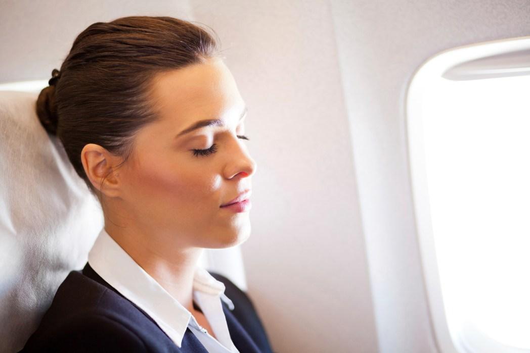 Kvinna vid fönsterplats ombord på flygplan