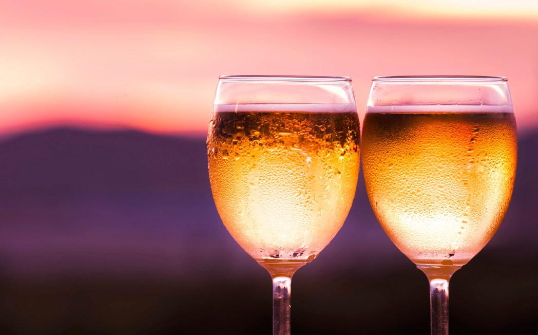 vinprovning med två kalla glas vitt vin i solnedgången