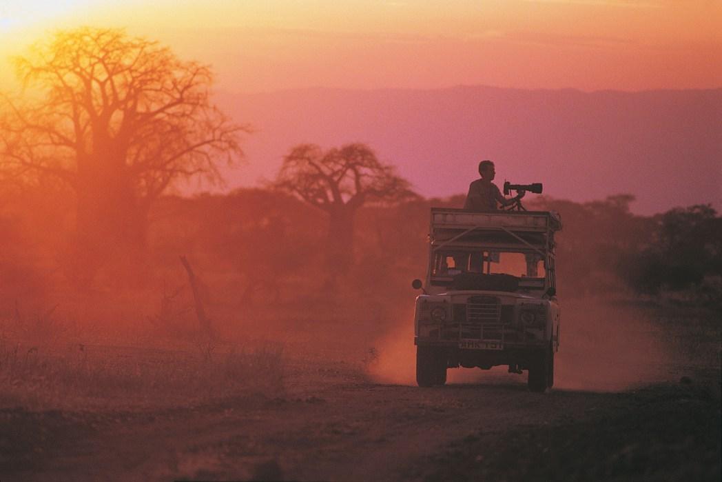 kameraman på taket av en jeep på safari i afrika i solnedgången