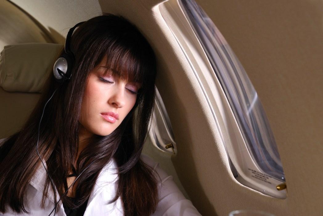Kvinna lyssnar på musik ombord på flygplan